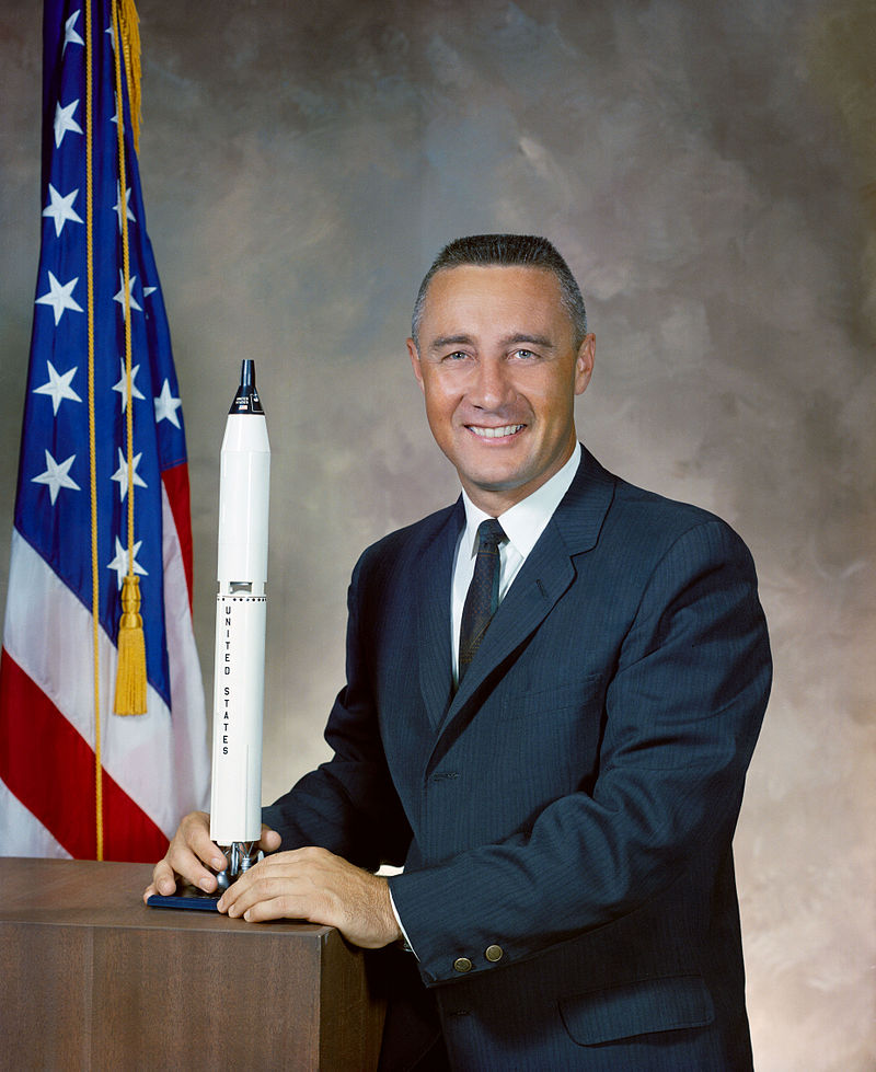 Gus Grissom holding replica space rocket with American flag in the background