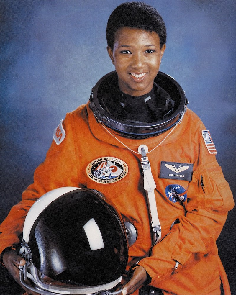 Mae Carol Jemison in an orange space suit holding their helmet to their side