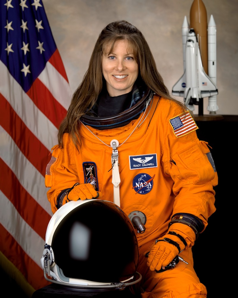 Tracy Caldwell in an orange space suit with their helment in front of them